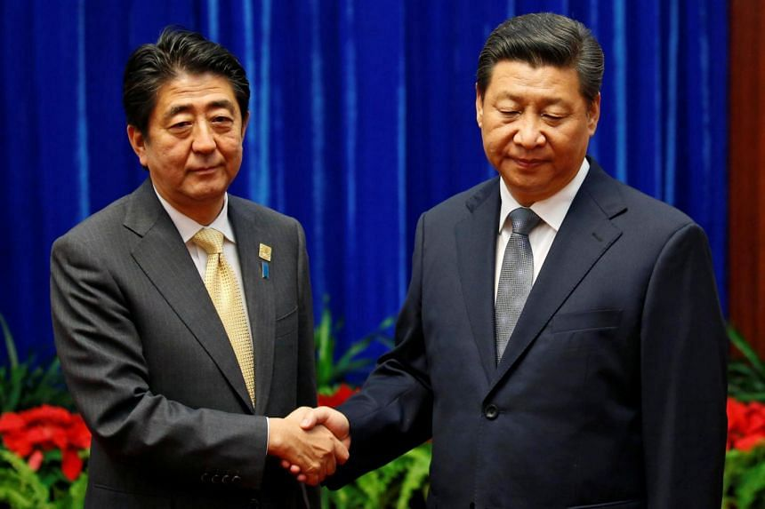 China's President Xi Jinping (right) shakes hands with Japan's Prime Minister Shinzo Abe during their meeting at the Great Hall of the People, in Beijing, on Nov 10, 2014.