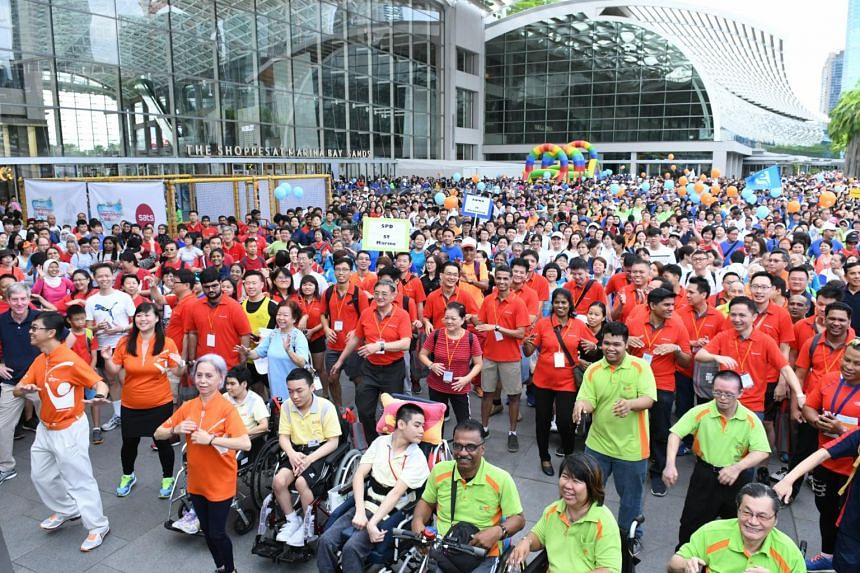 Members of the public gather at the event plaza for a warm up before the Community Chest Heartstrings Walk at the Marina Bay Sands on Sept 12, 2017.