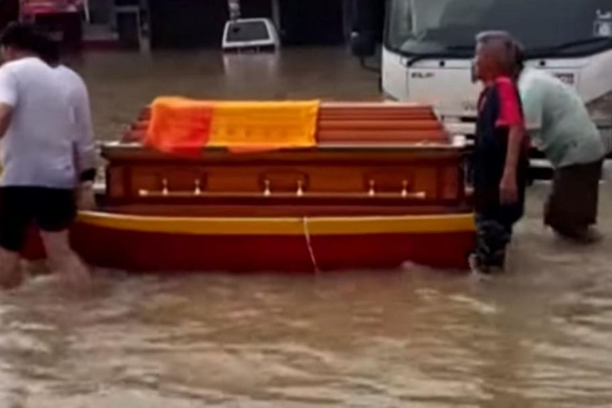 As floodwaters inundated the streets of Penang, one family was not deterred in giving a loved one a final sending off.