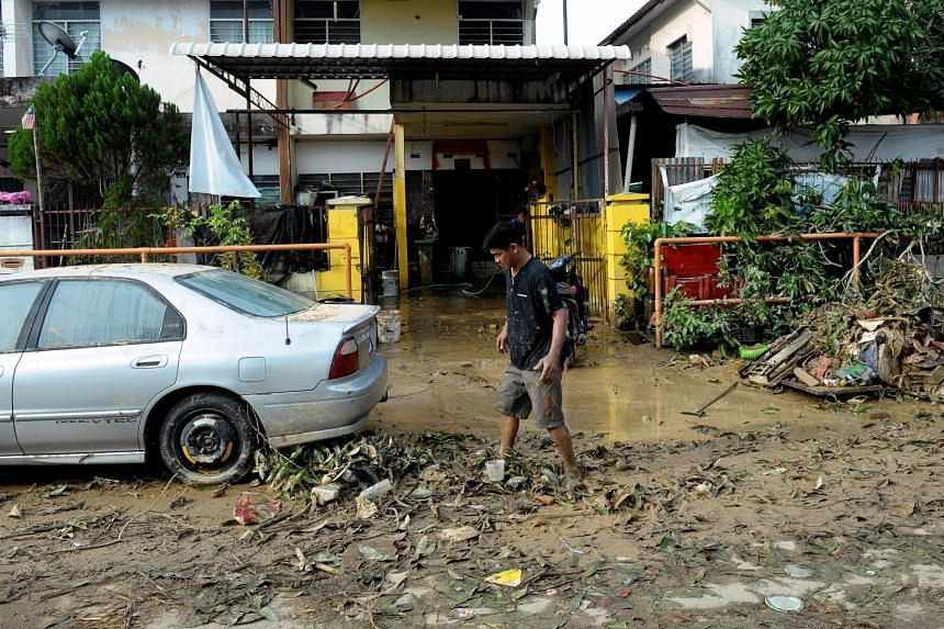 A man walks through a muddy road after a flood in George Town, Penang, on Nov 6, 2017.