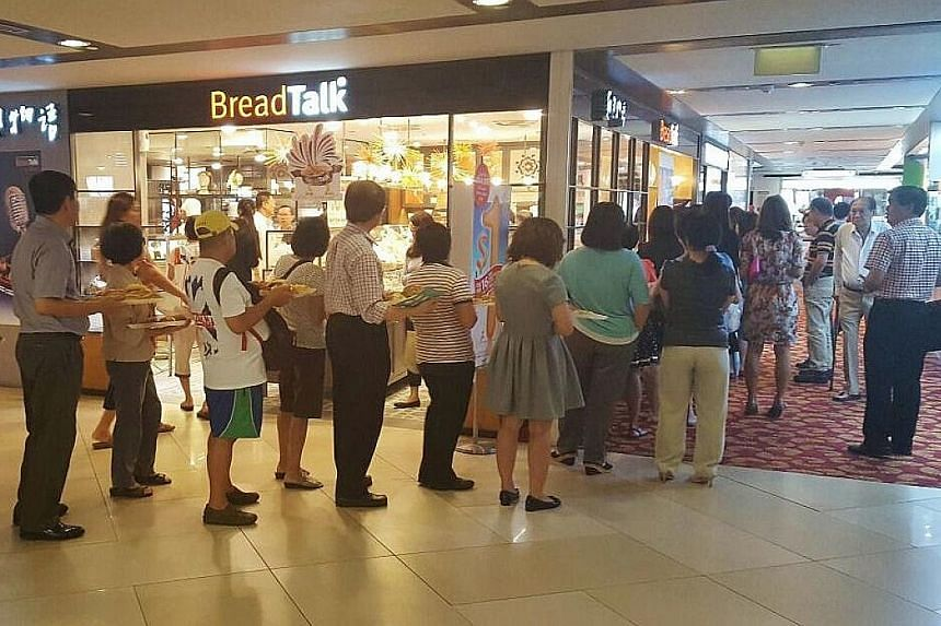Customers queueing at a BreadTalk outlet. Revenue at BreadTalk dipped 2 per cent for the three months to Sept 30, but the bottom line was boosted by a 7.1 per cent decrease in distribution and selling expenses for the quarter to $59.3 million from $6