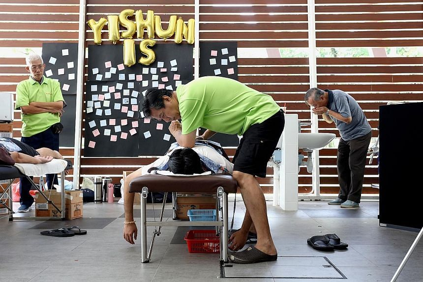 Mr Lim Yow Hoon, 61, giving a massage at Yishun Park Hawker Centre on Sunday as part of a fringe activity for the exhibition, This Is Yishun. Mr Lim, who gives free massages to residents living near his provision shop, is one of several residents fea