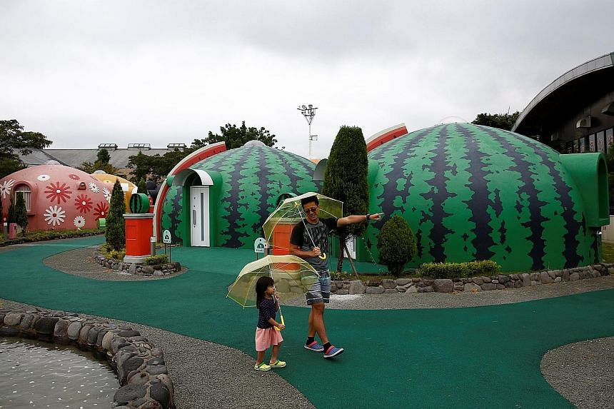 A family taking a walk around the quake-resistant dome houses at the Aso Farm Land resort in Aso, Kumamoto Prefecture, in September.