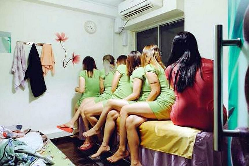 Women in a massage parlour during a police raid. In the past five years, about 12 per cent of people caught for abetting vice activities were involved in illegal brothels operating in HDB flats.