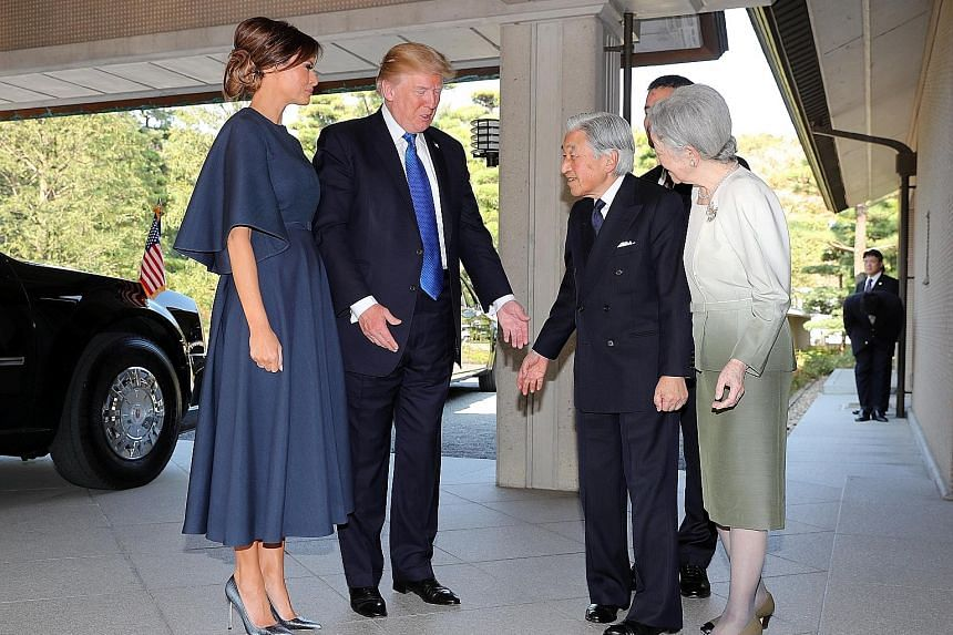 US President Donald Trump and First Lady Melania Trump being welcomed by Japanese Emperor Akihito and Empress Michiko on their arrival at the Imperial Palace in Tokyo yesterday.