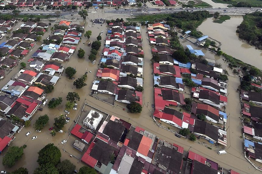 The view from a Malaysian Maritime Enforcement Agency helicopter shows the extent of the flood damage in a residential area in Penang yesterday. The number of evacuees in the state rose to 5,478. A resident making his way through a mud-filled road in