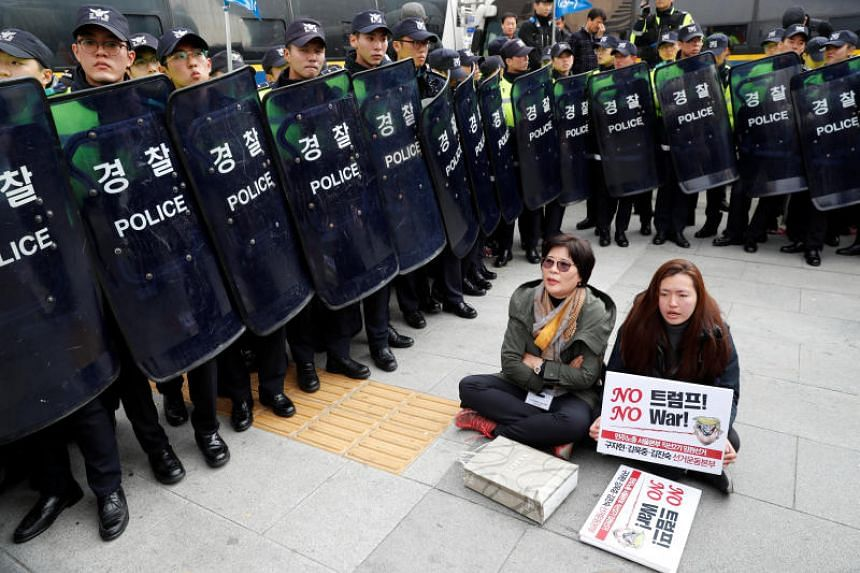 Police surround two protesters rallying against US President Donald Trump in central Seoul on Nov 7, 2017.