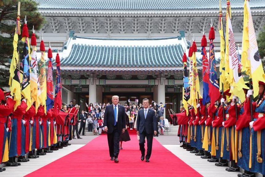 US President Donald Trump, accompanied by South Korean President Moon Jae In, reviews a traditional honour guard during a welcoming ceremony at the presidential office in Seoul on Nov 7, 2017.