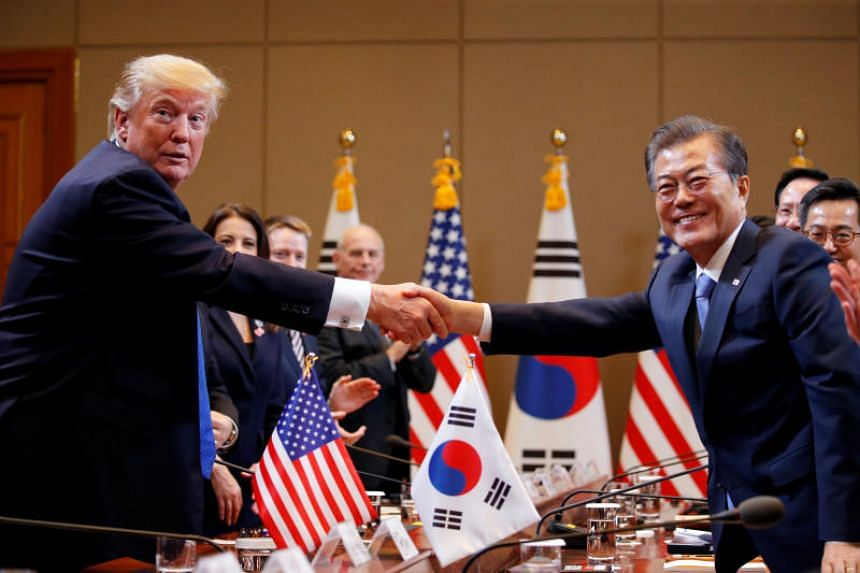 US President Donald Trump and South Korea's President Moon Jae In shake hands before the summit meeting at the Presidential Blue House in Seoul on Nov 7, 2017.