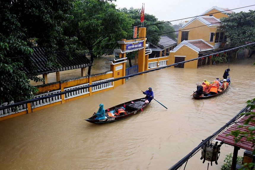 People ride boats along submerged houses in the UNESCO heritage ancient town of Hoi An after typhoon Damrey hits Vietnam on Nov 6, 2017.