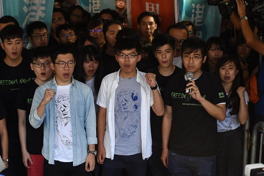 (From left) Nathan Law, Joshua Wong and Alex Chow, leaders of Hong Kong's Umbrella Movement, gesture as they address the media before their sentencing in Hong Kong.