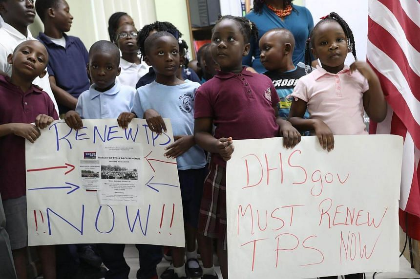 Children hold posters asking the Federal government to renew Temporary Protected Status during a press conference at the office of the Haitian Women of Miami in Florida.