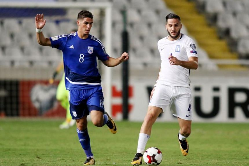 Greece's defender Kostas Manolas (right) attempts to clear the ball as he is marked by Cyprus' forward Pieros Sotiriou during their World Cup 2018 qualifying Group H football match between Cyprus and Greece at the NEO GSP Stadium in Nicosia on Oct 7,