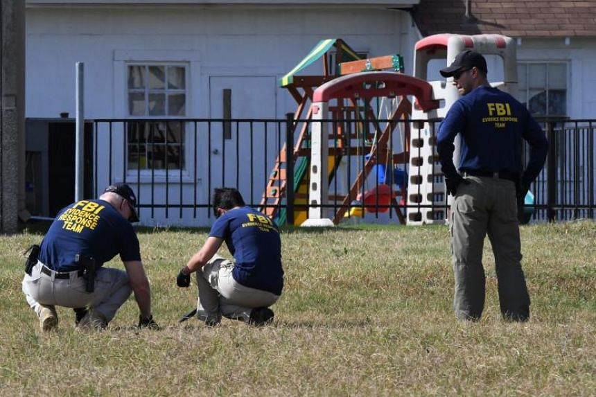 FBI agents search for clues at the entrance to the First Baptist Church, after a mass shooting that killed 26 people in Sutherland Springs, Texas on Nov 6, 2017.