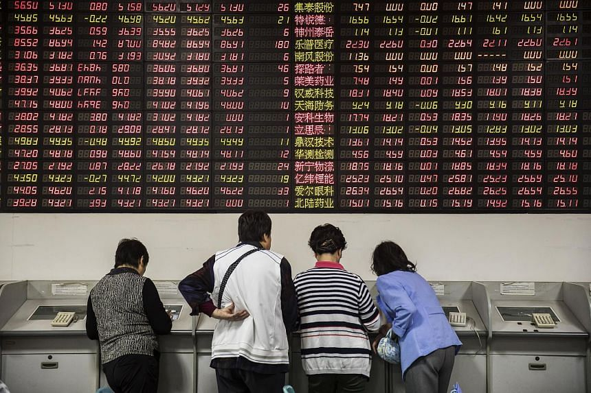 Investors stand at trading terminals in front of electronic stock boards at a securities brokerage in Shanghai.