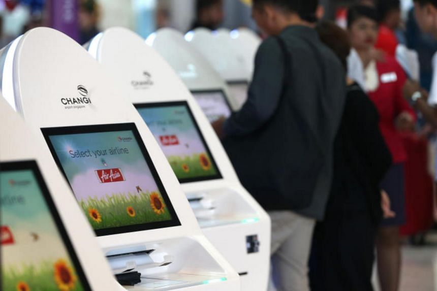 AirAsia passengers using automated check-in machines.