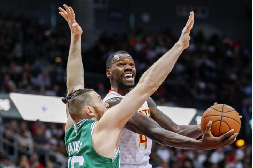 Atlanta Hawks center Dewayne Dedmon (right) in action against Boston Celtics center Aron Baynes (left) of Australia during the first half of the NBA basketball game at Philips Arena in Atlanta, Georgia, on Nov 6, 2017.