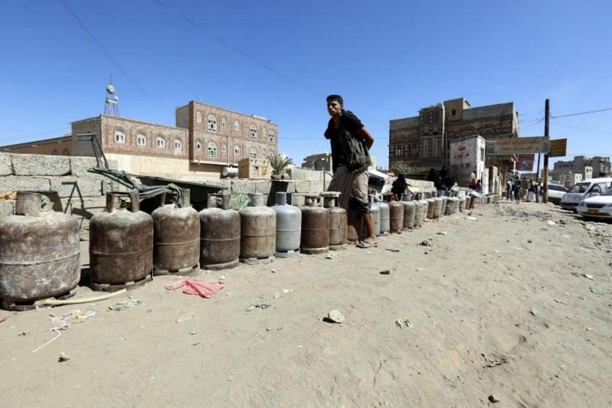 Yemenis wait next to empty gas cylinders for gas supplies at a gas station amid increasing gas shortages a day after the Saudi-led coalition decided to close off Yemen's borders, on Nov 7, 2017.