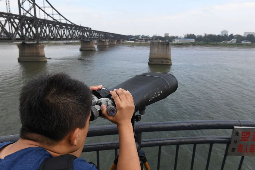 A tourist looking towards North Korea while visiting the Broken Bridge, in Dandong, China, on Sept 5, 2017.