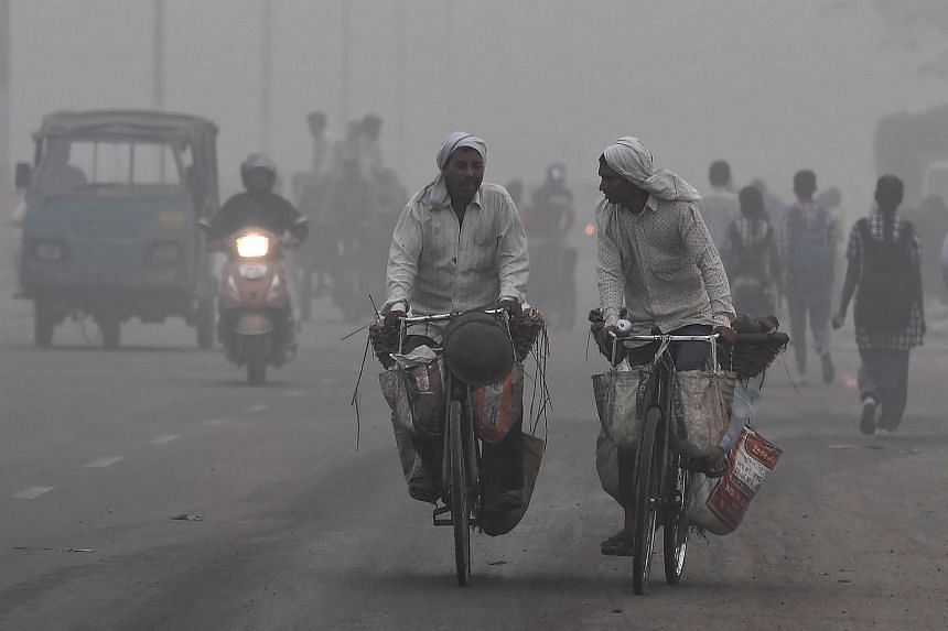 Indian commuters drive amid heavy smog in New Delhi on Nov 7, 2017.