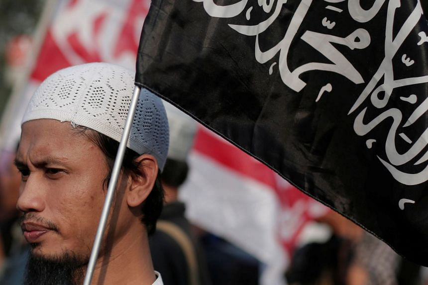 A man holds a Hizbut Tahrir Indonesia flag during a protest against the President Joko Widodo's decree to disband Islamist groups in Jakarta, on July 28.