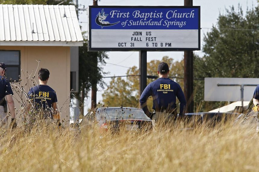 Members of the FBI use metal detectors to search the church grounds while investigators work at the scene of a mass shooting at the First Baptist Church in Sutherland Springs, Texas.