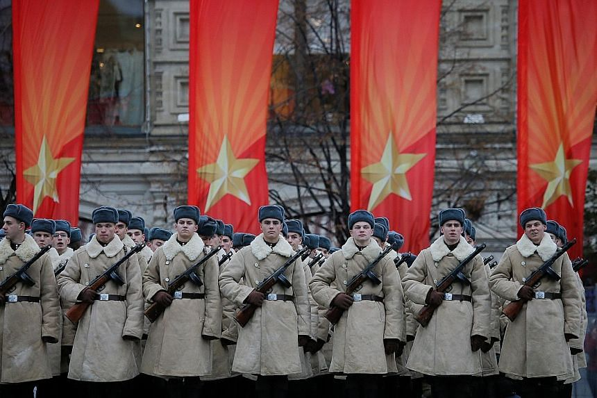 Servicemen dressed in historical uniforms at a military parade in Moscow's Red Square yesterday. The parade was billed as a re-enactment in vintage uniforms of a historic 1941 parade during World War II.