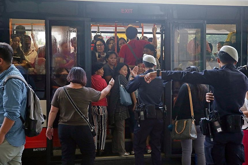 Commuters using a bridging bus service at Bishan station after MRT service was disrupted by a flooded tunnel on the morning of Oct 8.