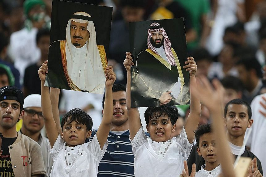 Football fans hold up portraits of King Salman and Prince Mohammed during a Fifa World Cup 2018 qualification match.