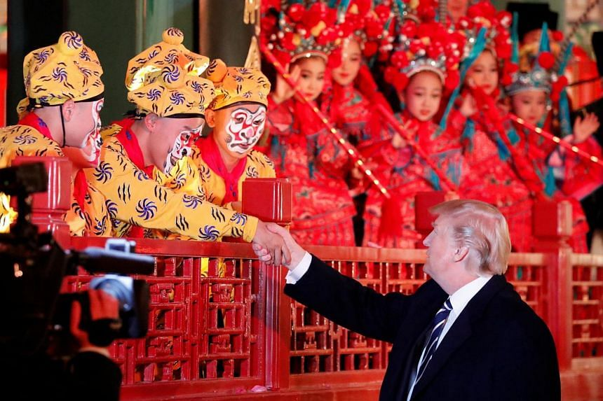 US President Donald Trump shakes hands with a performer at the Forbidden City in Beijing, China on Nov 8, 2017.