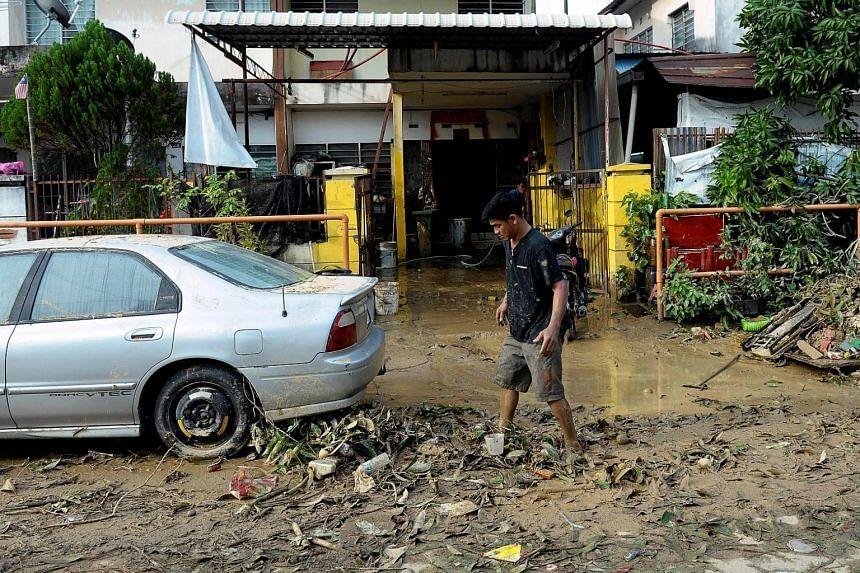A man walks through a muddy road after a flood in George Town, Penang, Malaysia on Nov 6, 2017.