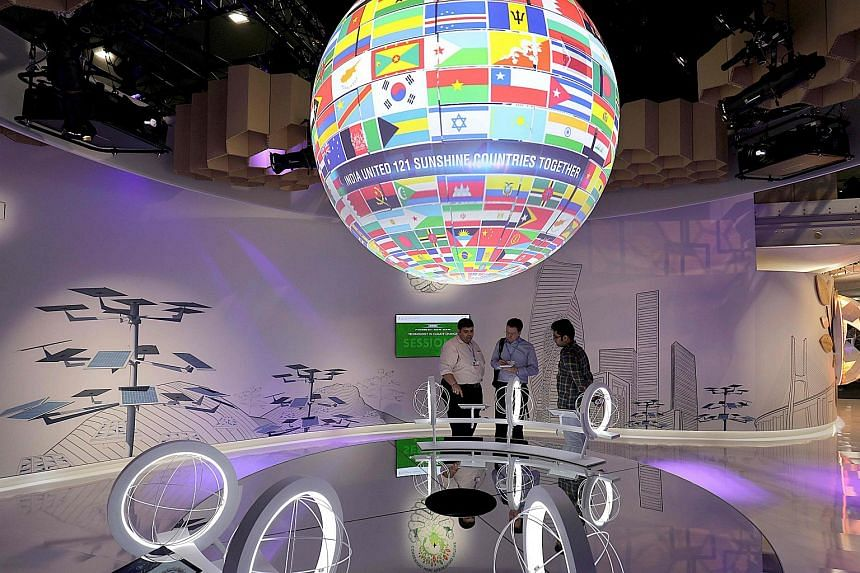 Visitors stand beneath a spinning globe with the flags of the nations during the COP23 United Nations Climate Change Conference.