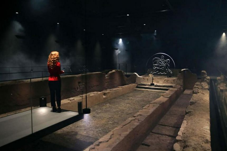An employee poses alongside a reconstruction of the Roman Temple of Mithras at the London Mithraeum, Bloomberg SPACE, at the new Bloomberg headquarters in central London on Nov 7, 2017.
