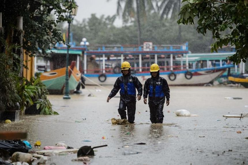 Electric workers wade through a flooded street in the town of Hoi An on Nov 8, 2017.
