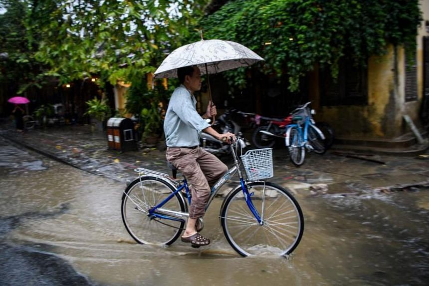 A man rides a bicycle in the town of Hoi An on Nov 8, 2017.
