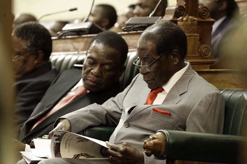 Zimbabwe President Robert Mugabe (right) reading a copy of the national budget with then Vice-President Emmerson Mnangagwa on Dec 8, 2016.