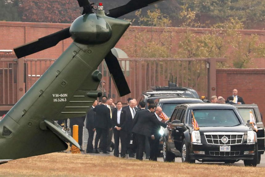 White House senior staff discuss the situation as US President Donald Trump sits in his car after being grounded from an attempt to visit the Demilitarized Zone (DMZ) in the truce village of Panmunjom dividing North Korea and South Korea.