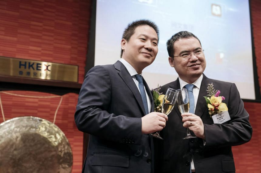 Liang Xiaodong (left), co-chief executive officer of China Literature Ltd. and Wu Wenhui, co-chief executive officer, pose for a photograph while holding glasses of champagne during the company's listing ceremony at the Hong Kong Stock Exchange.