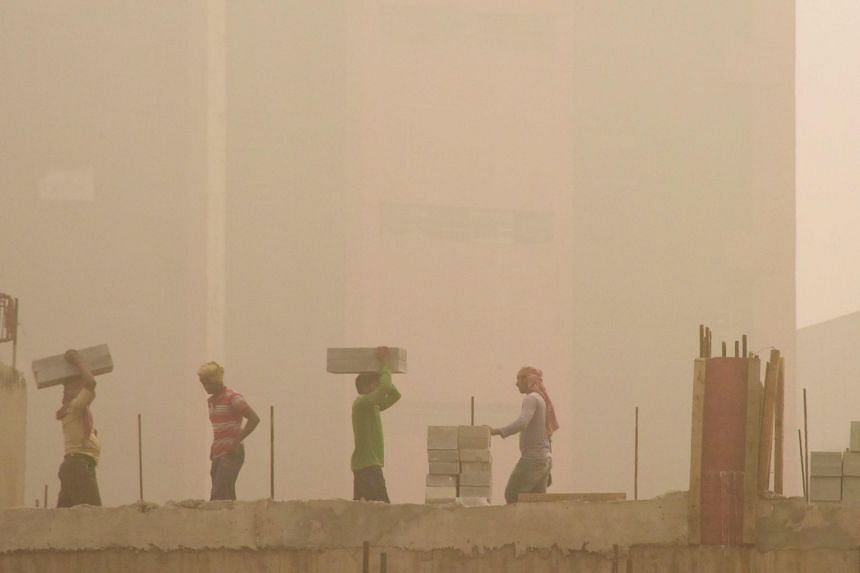 Indian labourers work on a construction site during heavy smog conditions in New Delhi on Nov 7, 2017.