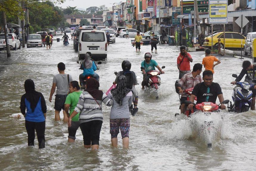 People walking in the floodwater at Taman Desa Murni in Sungai Dua.