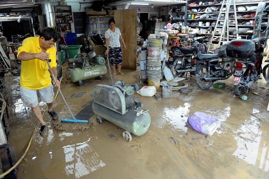 People cleaning mud away from their shop after a flood in Georgetown, Penang.