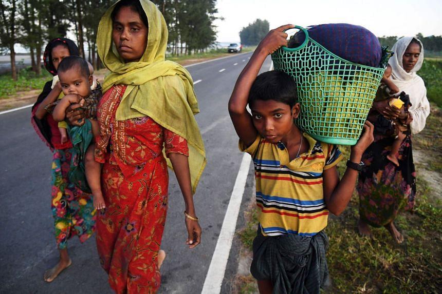 Rohingya Muslim refugees who were entered Bangladesh by boat walk towards refugee camps after landing in the Bangladeshi district of Teknaf.