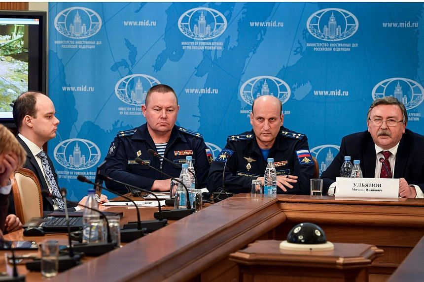 Russian Foreign Ministry's security and disarmament department head Mikhail Ulyanov (right) along with other attendees hold a briefing to present analysis of the report by UN investigators which blamed a sarin gas attack in Syria's Khan Sheikhun on B