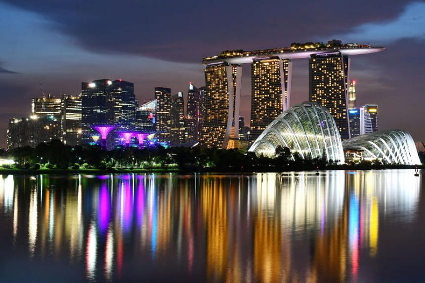 Night view of the Singapore skyline, including Gardens by the Bay, Marina Bay Sands, Central Business District, and Marina Bay Financial Centre.