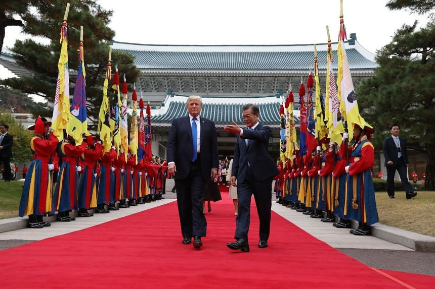 US President Donald Trump and his South Korean counterpart, Mr Moon Jae In, walking past an honour guard at a welcoming ceremony at the presidential Blue House in Seoul yesterday.
