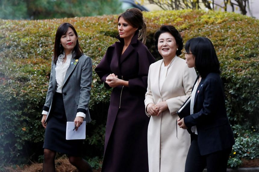 US First Lady Melania Trump and South Korea's First Lady Kim Jung Sook (in white) taking a walk in the grounds of the Blue House yesterday. President Trump's visit to he country is part of a 12-day Asian tour.