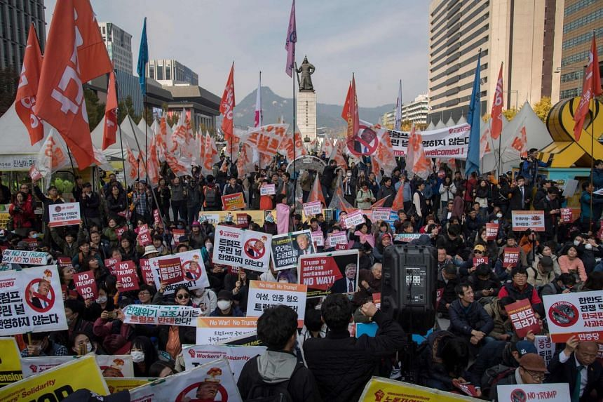 Anti-Trump protesters shouting slogans while waiting for President Trump's convoy to pass by in Seoul's Gwanghwamun Square yesterday.