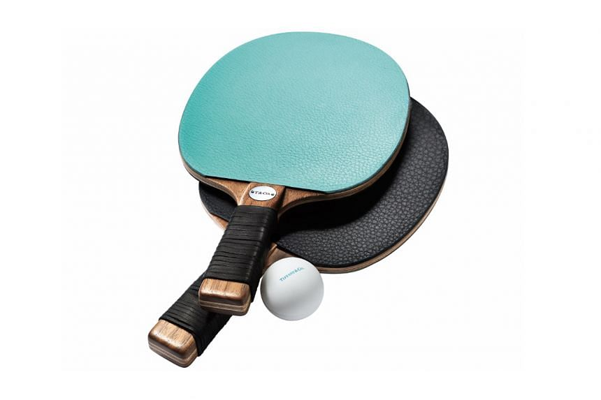 "Tiffany & Co's new Home & Accessories collection includes a ""paper"" cup, a ball of yarn and table tennis bats (above)."