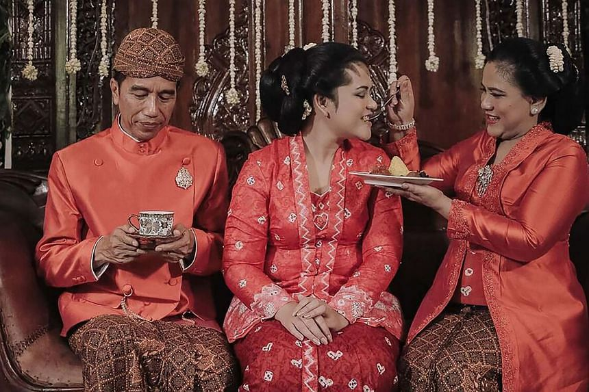 Indonesia's First Lady Iriana Widodo (right) feeding her daughter Kahiyang Ayu (centre) beside Indonesia's President Joko Widodo during preparations for the wedding of Kahiyang Ayu in Solo, Central Java.