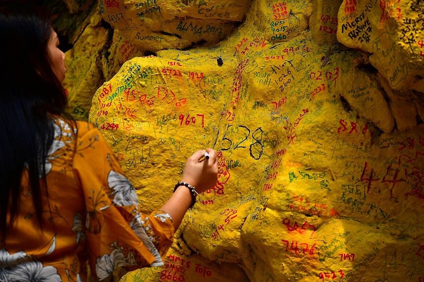 Devotees at the Da Bo Gong temple. Figures from the Singapore Land Authority show that over the past five years, about 42,000 people visited Kusu Island during the pilgrimage season each year. A devotee writing numbers and wishes on the surface of a